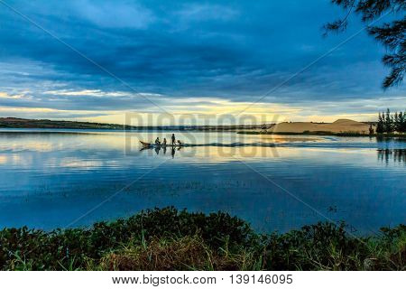 People on a small boat gliding across a glassy blue lake under a blue sky at twilight in Vietnam
