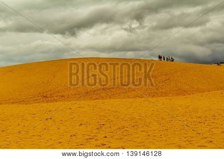 A group of people standing on sand dunes on a cloudy day in Vietnam