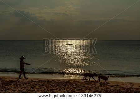 A silhouetted Vietnamese woman walks on a beach at sunset while a rafter glides past