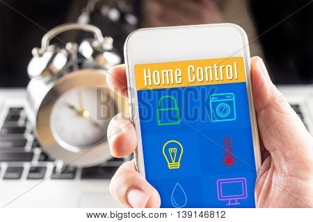 Hand Holding Smart Phone With Home Control Application With Clock And Computer At Background, Smart
