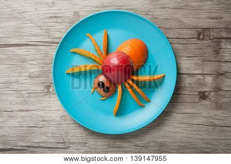 Spider made of juicy fruits on plate and desk