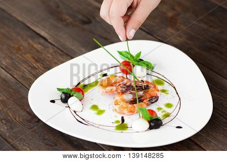 Hand decorated plate with grilled shrimps with green sticks, dark wooden background. Food preparation before serving at restaurant