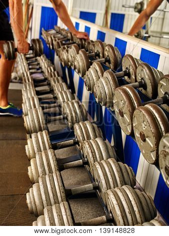 A lot of dumbbells in sport gym. Male hands lift dumbbells in sport gym.