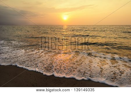 Ocean sunset is the setting sun throwing a brilliant golden light reflecting off the water as a gentle wave rolls to the shore.