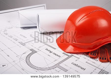 Construction helmet and protective gloves, construction of the building layout, building drawing on paper, protective clothing, drawings rolled in a roll