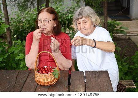 Senior citizens enjoying their day eating cherries