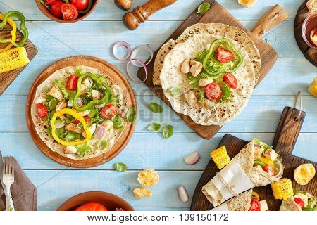 Tortilla with grilled chicken fillet and grilled vegetables on a blue wooden table outdoors. Top view. Outdoors Food Concept