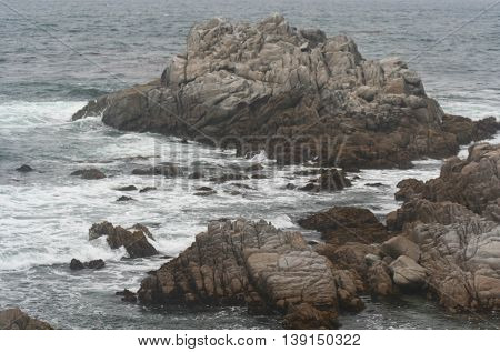 Two groupings of brown jagged rocks surrounded by blue grey water and white foam along the coast of Pacific Grove, California.