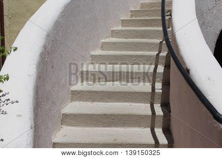 Section of curved white stucco staircase outdoors with black railing