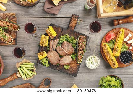 Different foods cooked on the grill with red wine steaks zucchini stuffed with meat vegetables snacks for wine and sauce on wooden table