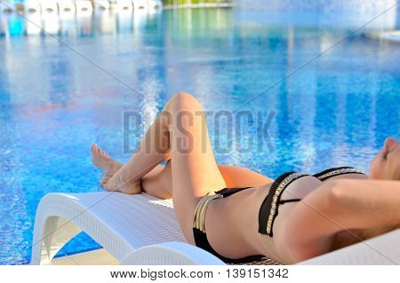Leisure Time. Beautiful Young Woman Lying On The Deck Chair Near The Pool. Focus On Feet