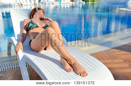 Young Woman Lying On A Lounger Near The Swimming Pool. Focus On Feet