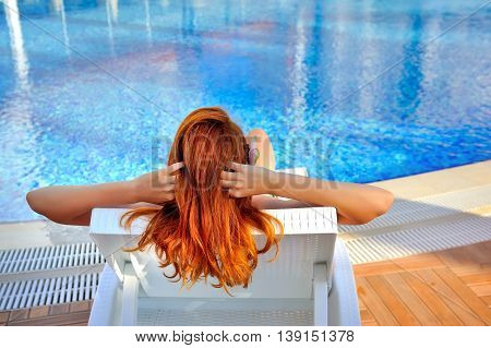 The Young Red-haired Woman Lying On A Lounger Near The Swimming Pool