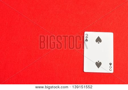 Playing card. Two of spades isolated on a red background