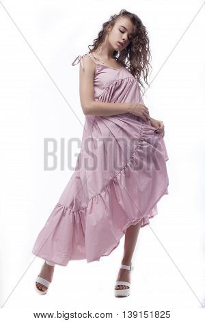 A beautiful young woman standing full length in a summer dress, isolated for white background.