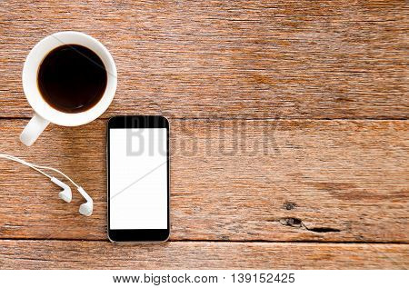 Smart phone and Earphone with coffee on wooden floor.Top view focus.