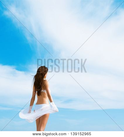 Beautiful woman in white bikini. Young and sporty girl posing on a beach at summer.