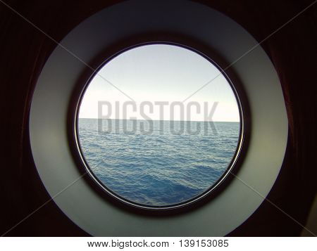 Porthole into the open sea from a cruise ship.