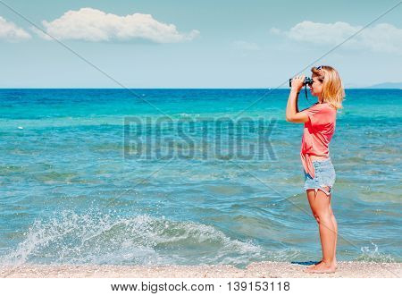 Beautiful young woman with binoculars on the sea background