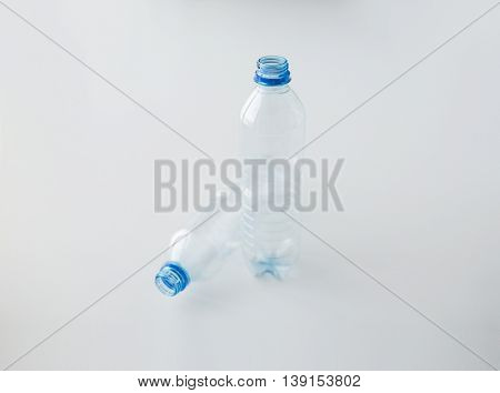 recycling, healthy eating and food storage concept - close up of clean empty used plastic water bottles on table