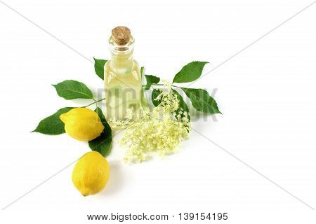 Sambucus nigra elderberry sirup on white background. Bottle of excellent syrup with flowers leaves and lemon.