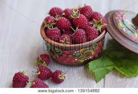 Ripe sweet raspberries in bowl on wooden table. Flat lay.