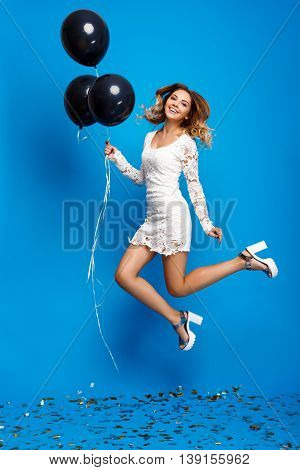 Portrait of young beautiful blonde girl in dress looking at camera, jumping, holding baloons, smiling, resting at party over blue background.
