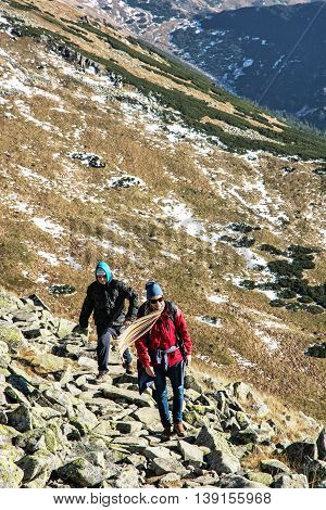 Young woman with son on the mountain footpath leading up the peak Dumbier Low Tatras Slovak republic. Hiking theme. Mountains scene. Travelers on the stoned sidewalk.