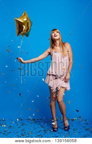 Portrait of young beautiful girl in dress holding baloon, smiling, resting at party over blue background.