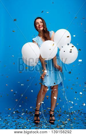 Portrait of young beautiful brunette girl in dress looking at camera, holding baloons, smiling, resting at party over blue background.