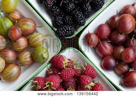 fresh ripe raspberries,mulberries, gooseberries on a wooden background
