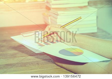 Businessman analyzing Business charts on a wooden desk at home