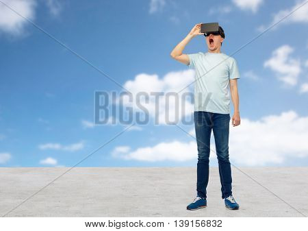 3d technology, virtual reality, entertainment, cyberspace and people concept - amazed young man with virtual reality headset or 3d glasses looking at something over blue sky and clouds background