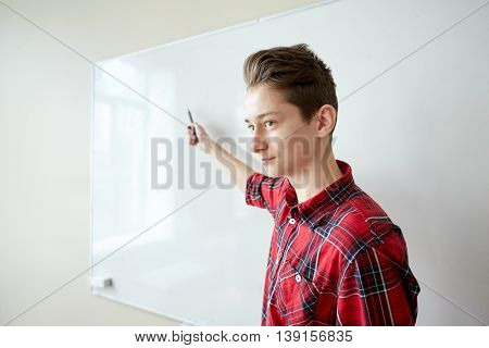 education, school, learning and people concept - student boy with marker showing something on blank white board
