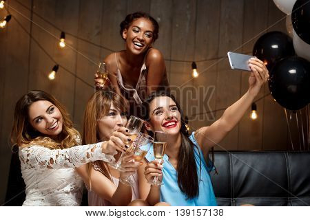 Four young beautiful girls in dresses making selfie, smiling, laughing  at party.
