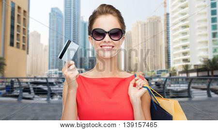 people, finances, tourism, travel and sale concept - young happy woman with shopping bags and credit card over dubai city skyscrapers background