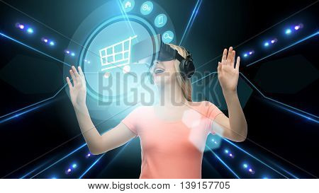 technology, virtual reality, cyberspace and people concept - happy young woman with virtual reality headset or 3d glasses looking at shopping cart icon over black background and lights