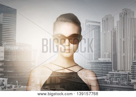 accessories, eyewear, fashion, people and luxury concept - beautiful young woman in elegant black sunglasses over dubai city with double exposure background