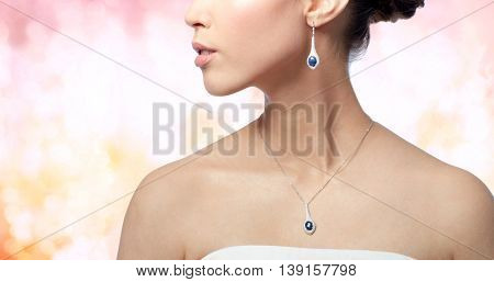 beauty, jewelry, wedding accessories, people and luxury concept - close up of beautiful asian woman or bride with earring and pendant over holidays lights background