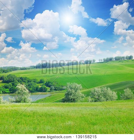 picturesque hills forest and sun on blue sky