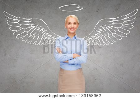 business, angel investor, safety, security and people concept - smiling young businesswoman with wings and nimbus drawing over gray concrete background