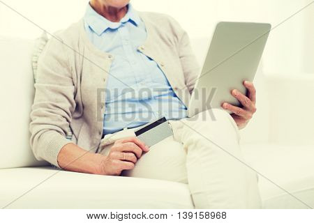 technology, online shopping, age and people concept - close up of senior woman with tablet pc computer and credit or bank card at home