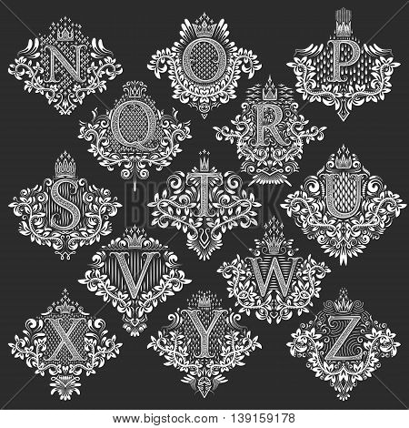Set of heraldic monograms in coats of arms form. White floral decorative stamps of letters from N to Z. Isolated tattoo labels in vintage baroque style.