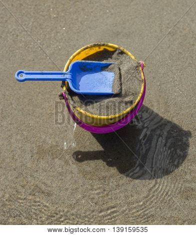 Toy Spade and Bucket on a Beach with sand.