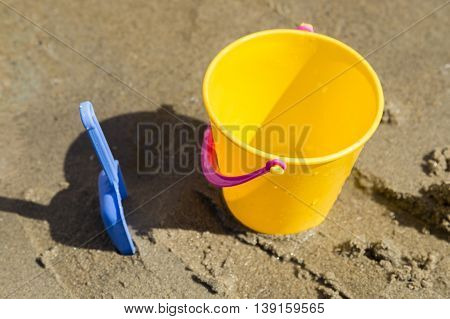 A Toy Spade and Bucket in Sand.