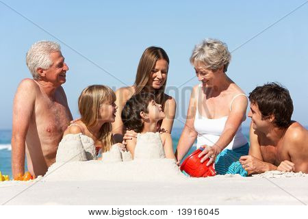 Three Generation Family Building Sandcastles On Beach Holiday
