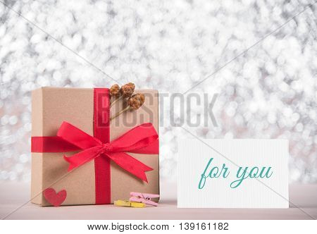 Picture of gift box with red ribbon and message love you on greeting card blur bokeh gray background. congratulation valentine day concept