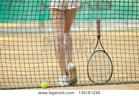 Clay tennis court with tennis player legs,ball, netting, racket.