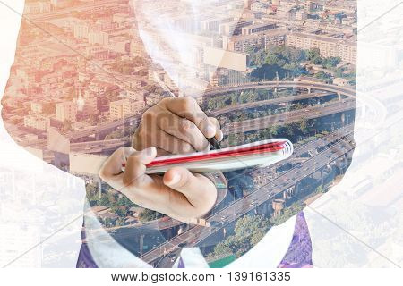 Double exposure of businesswoman  writing the word on a notebook on cityscape background.
