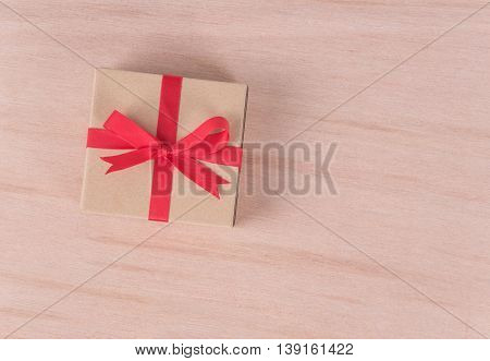 Vintage gift box with red ribbon on wooden background. congratulation concept